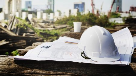 hard hat and paper plans in foreground, construction site in background
