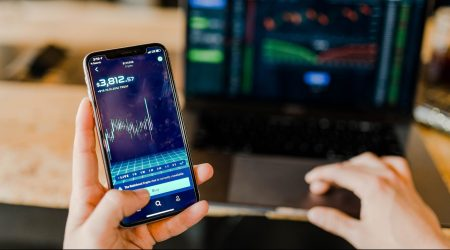 laptop and phone screen with stock market figures
