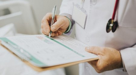 close up of doctor writing on chart